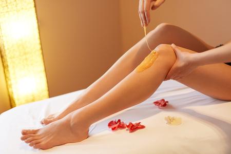 depilacion con cera: Piernas largas de la mujer. Mujer cuida sobre sus piernas. Adición de sacarosa Tratamiento Foto de archivo