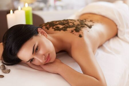 spa woman: Spa Woman. Brunette Getting a Marine Algae Wrap Treatment in Spa Salon