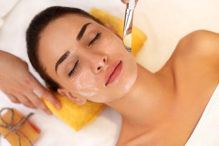 美しさ: 顔治療。美容室で女性が海洋のマスクを取得します