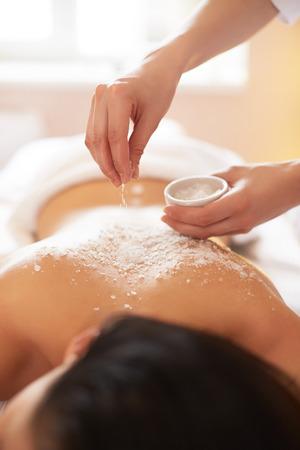 sal: Spa mujer. Brunette Conseguir un tratamiento de belleza sal Scrub en el Spa. Exfoliación corporal. Foto de archivo