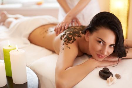 body: Spa Woman. Brunette Getting a Marine Algae Wrap Treatment in Spa Salon