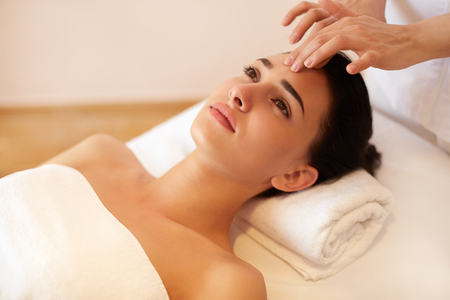 skönhet: Vacker ung kvinna som får en ansiktsbehandling på skönhetssalong. Stockfoto