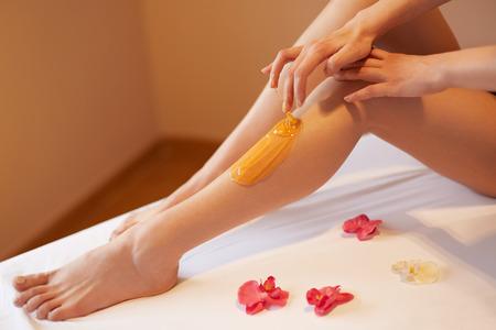 azucar: Piernas largas de la mujer. Mujer cuida sobre sus piernas. Adición de sacarosa Tratamiento Foto de archivo