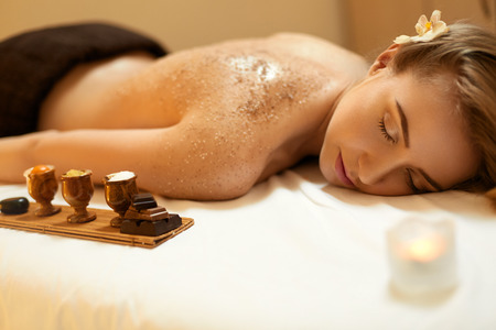 cuerpo humano: Exfoliación corporal. Hermosa Rubia Obtiene un tratamiento de belleza sal Scrub en el Salón de spa