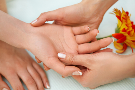 woman relaxing: Hand Massage. Blonde Gets Spa Treatment in Salon.