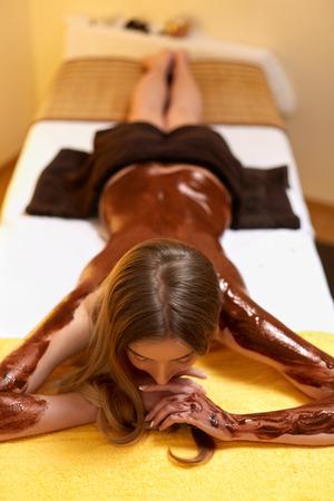 chocolate mask: Spa Woman. Young Woman Gets Chocolate Body Mask at Beauty Salon Stock Photo