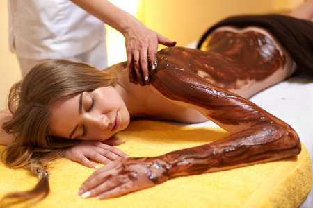 Spa Woman. Young Woman Gets Chocolate Body Mask at Beauty Salon Stock Photo