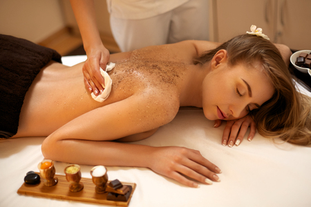 woman in spa: Body Scrub. Beautiful Blonde Gets a Salt Scrub Beauty Treatment in the spa Salon