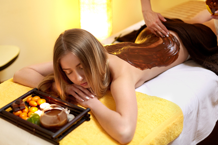 Spa Woman. Young Woman Gets Chocolate Body Mask at Beauty Salon Zdjęcie Seryjne