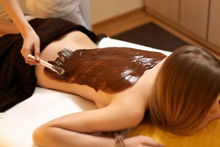 body mask: Spa Woman. Young Woman Gets Chocolate Body Mask at Beauty Salon Stock Photo