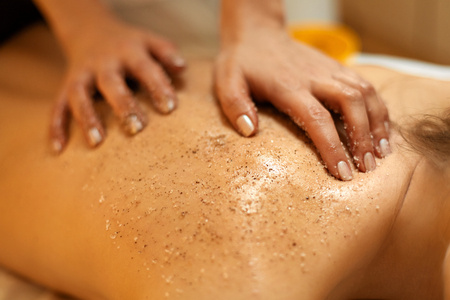 sal: Exfoliación corporal. Hermosa Rubia Obtiene un tratamiento de belleza sal Scrub en el Salón de spa
