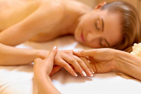 treatment: Hand Massage. Beautiful Blonde Gets Spa Treatment in Salon. Stock Photo