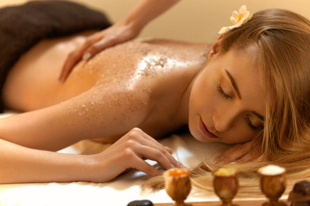 spa treatments: Body Scrub. Beautiful Blonde Gets a Salt Scrub Beauty Treatment in the spa Salon