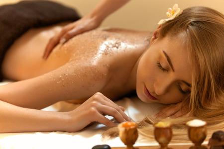 Body Scrub. Schöne Blonde Ruft einen Salzpeeling Kosmetische Behandlung im Wellness-Salon