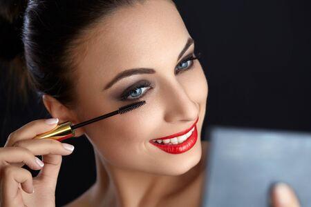 makeup eyes: Make-up. Beautiful Woman Doing Makeup. Mascara Brush. Red Lips