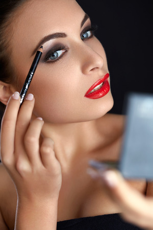 eyebrow: Make-up. Beautiful Woman Doing Makeup. Eyebrow Pencil. Red Lips Stock Photo