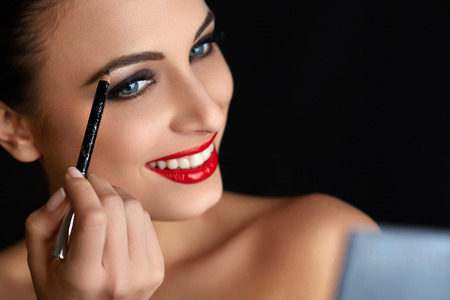 maquillaje de ojos: Maquillaje. Mujer hermosa que hace maquillaje. Lápiz de cejas. Labios rojos