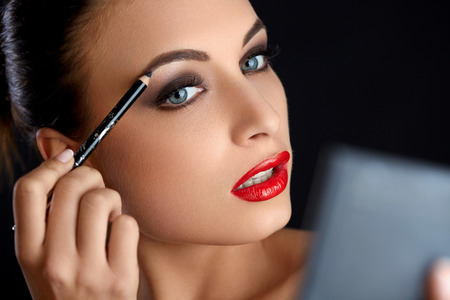 female eyes: Make-up. Beautiful Woman Doing Makeup Eyebrow Pencil. Red Lips Stock Photo