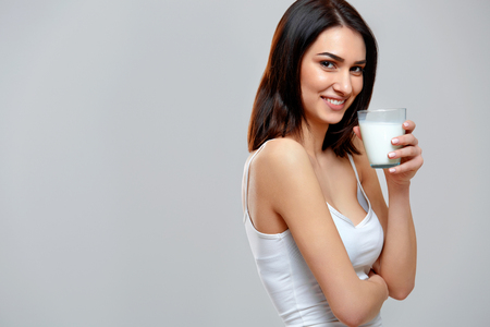drinks: Happy young woman drinking milk Stock Photo
