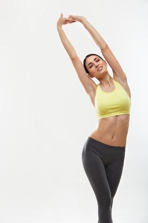 фитнес: Женщина делает упражнения на растяжку на белом