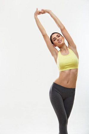 Woman doing stretching exercises against white Archivio Fotografico