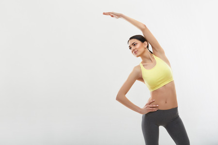 meditating woman: Woman doing stretching exercises against white Stock Photo