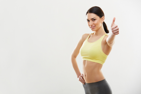 fitnes: Szczęśliwy przydatności Młoda kobieta pokazując kciuk do góry. Zdjęcie Seryjne