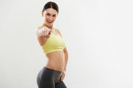 cuerpo femenino: Deporte de la mujer que señala en usted contra el fondo blanco Foto de archivo