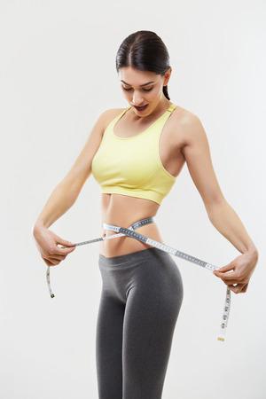 cintas: Mujer deportiva hermosa con cinta métrica Foto de archivo