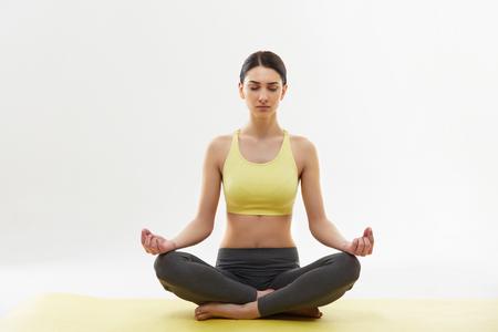 Vrouw mediteren en het doen Yoga tegen een witte achtergrond Stockfoto