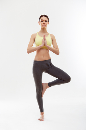 Young woman Doing Yoga Against White background photo