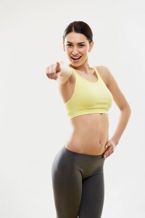 Sport Woman Pointing on You Against White Background photo