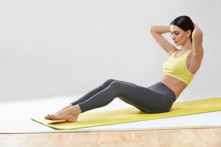 Woman doing stretching exercises against white photo