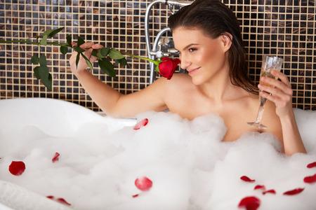 bañarse: Hermosa mujer tiene baño de burbujas.