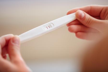 prueba de embarazo: Mujer que sostiene la prueba de embarazo