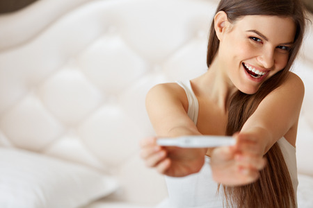 prueba de embarazo: Mujer feliz con la prueba de embarazo