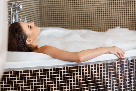woman in bath: Woman Relaxing in Bubble Bath. Body Care Stock Photo