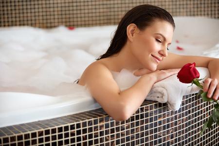 woman in bath: Beautiful Woman Relaxing in Bath With Rose