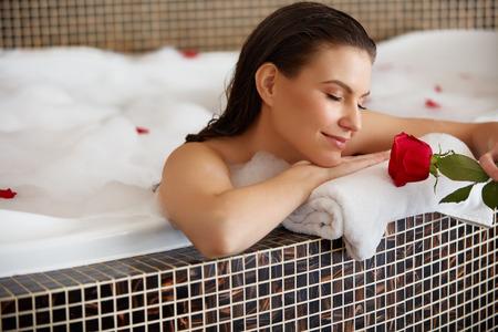 mujer con rosas: Hermosa mujer relajante en el baño con Rose
