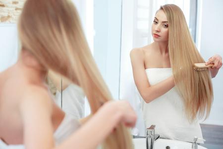 smooth hair: Beautiful Blond Brushing Her Hair
