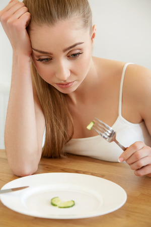 small plate: Beautiful Young Woman eats vegetable