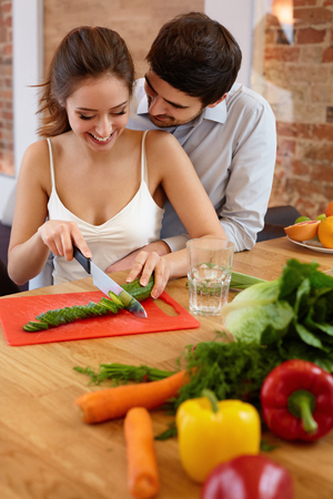 pareja comiendo: Pares que cocinan el alimento en cocina. Estilo de vida saludable