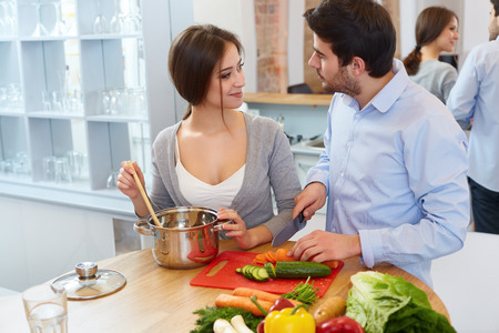 vegetables young couple: Couple Cooking Food in Kitchen. Healthy lifestyle Stock Photo