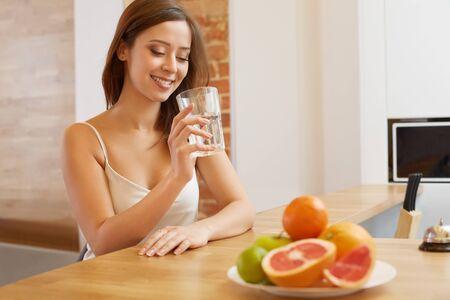 tomando agua: Mujer joven con un vaso de agua. Estilo de vida saludable