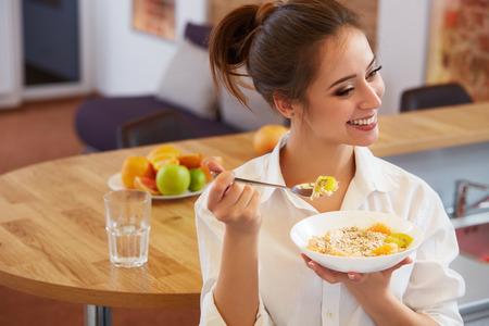 food: Mulher feliz que come o pequeno almoço saudável. Comida saudável Banco de Imagens