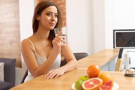 vaso con agua: Mujer joven con un vaso de agua. Estilo de vida saludable