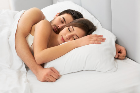 beds: Young happy couple sleeping in bed