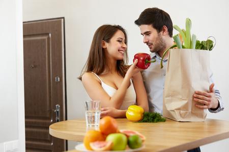 lifestyle: Jeune couple avec Grossery sac plein de légumes. Mode de vie sain