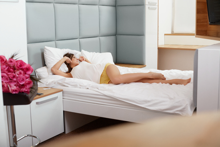 woman in bed: Young Woman Waking Up and Stretching In The Morning
