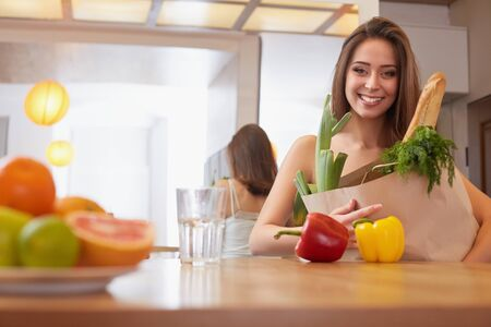 paper bag: Woman Holding Shopping Bag With Vegetables Standing in the Kitchen